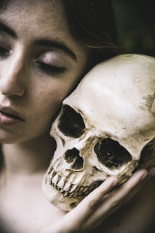 Woman with closed eyes holding skull
