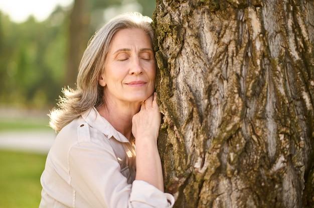 나무에 기대어 눈을 감고 있는 여자