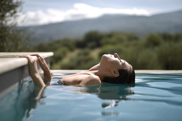 目を閉じてプールに頭を傾けている女性