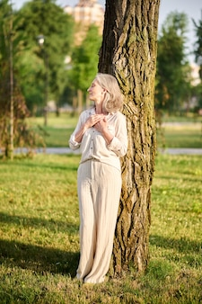 Woman with closed eyes leaning on tree
