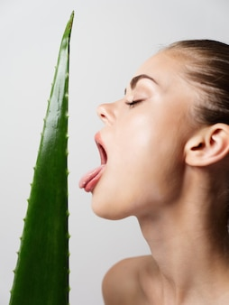 Woman with closed eyes licks aloe leaf on light background cropped view