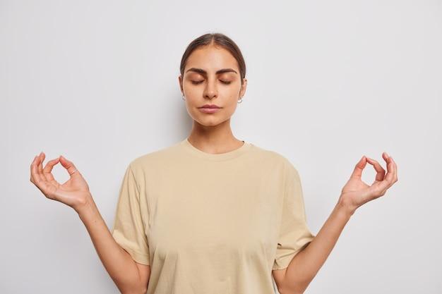 Женщина с закрытыми глазами медитирует, делает жест дзен, одетая в повседневную бежевую футболку, позирует на белом
