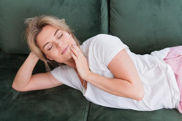 Donna con gli occhi chiusi, seduta sul divano