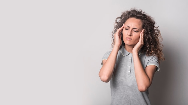 Woman with closed eyes suffering from headache against gray background