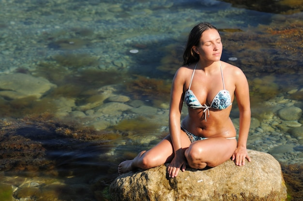 Woman with closed eyes, in swimsuit sitting on stones on seashore