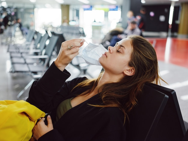 Woman with closed eyes takes off medical mask means airport passenger