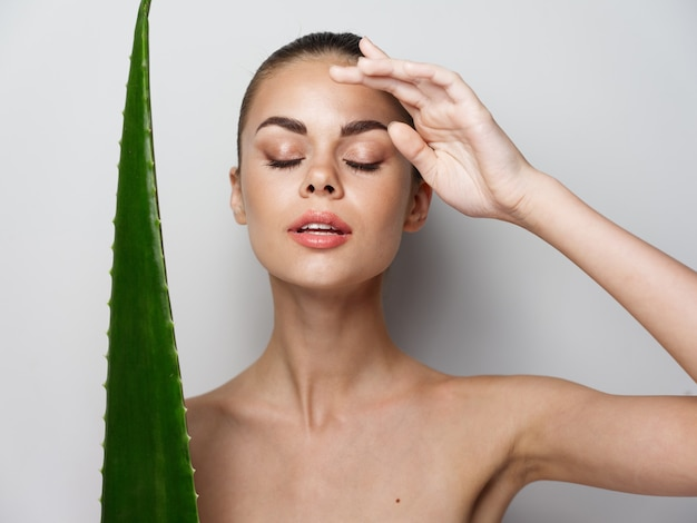 Woman with closed eyes touches face with hand and aloe leaf on light background