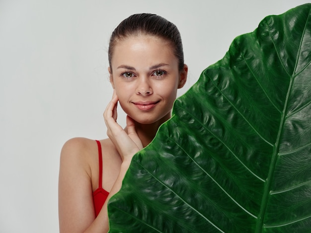 手と緑の葉のヤシの木の澄んだ肌で顔に触れる目を閉じた女性