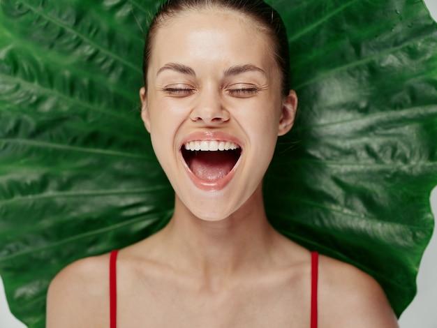 目を閉じて口を大きく開けて楽しむ女性がヤシの葉をクローズアップ