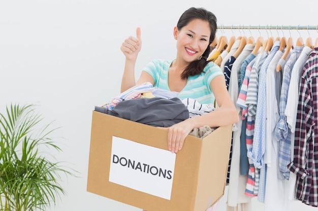 Женщина с пожертвованием одежды gesturing палец вверх