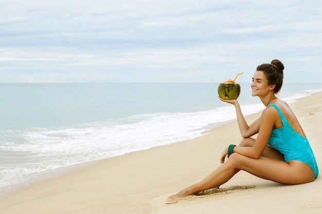 Woman with a coconut on the beach