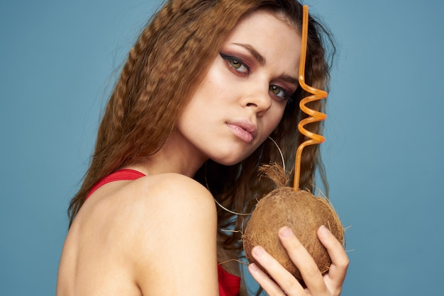 Woman with coconut cocktail in hands wavy hair bright makeup lifestyle studio summer vacation.