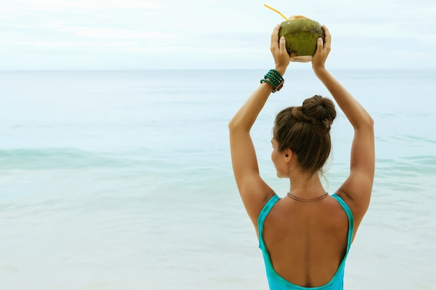 Woman with a coconut drink on the beach