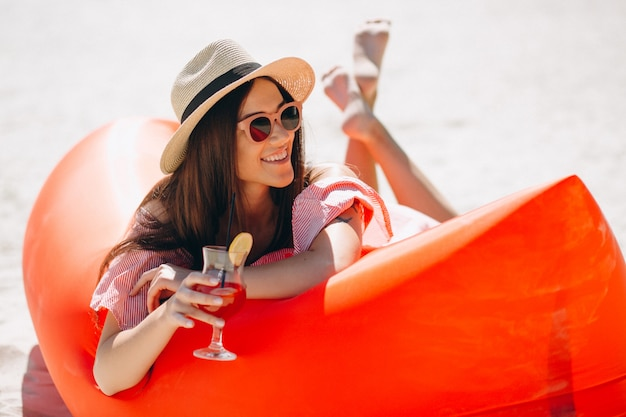 Woman with coctail in hat at the beach