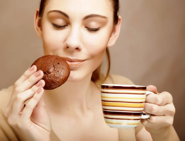 コーヒーとクッキーを持つ女性