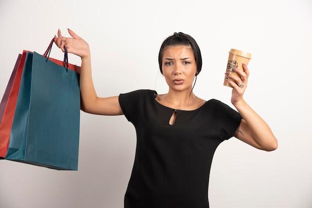 Женщина с кофе и хозяйственными сумками, чувствуя себя потерянной на белой стене.
