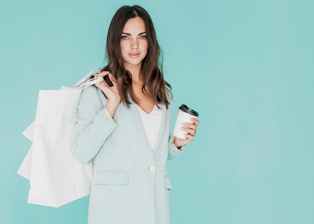 コーヒーと肩に買い物袋を持つ女性