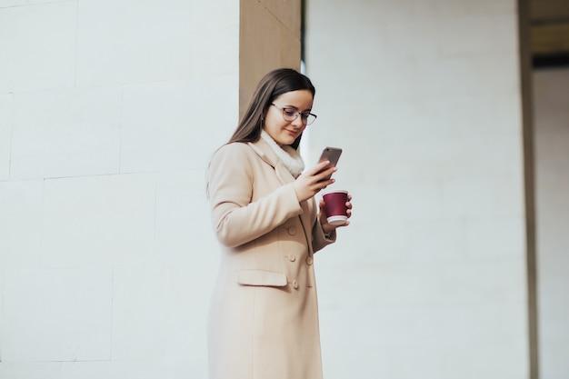 建物の近くに立っているコーヒーカップとスマートフォンを持つ女性