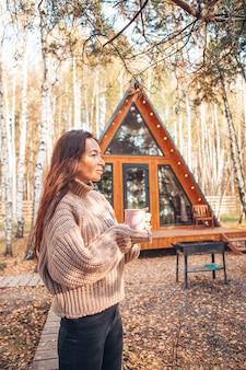Woman with coffee enjoying autumn day background of her house