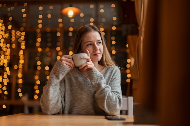 Woman with coffee looking on window