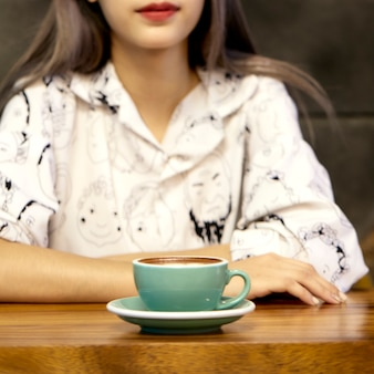 Женщина с кофейной кружкой горячий латте арт