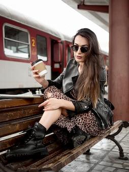 Женщина с кофе на скамейке