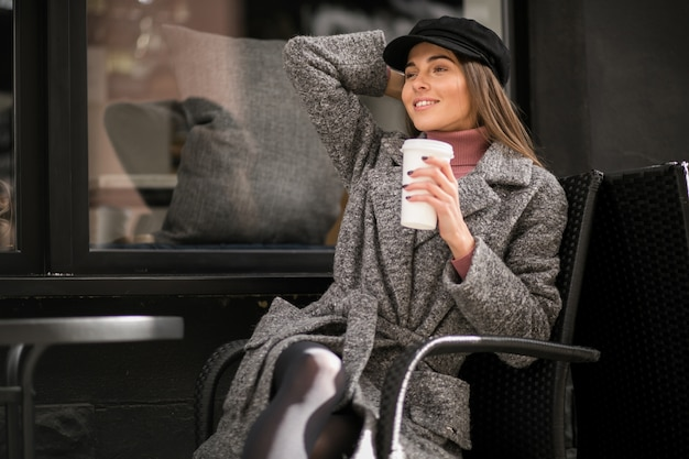 Woman with coffee sitting outside the cafe