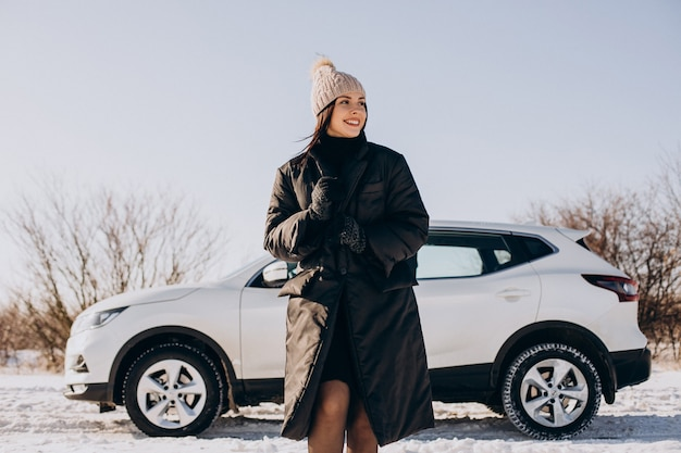 Woman with coffee standing by car in a winter field