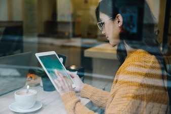 Woman with coffee tapping tablet screen