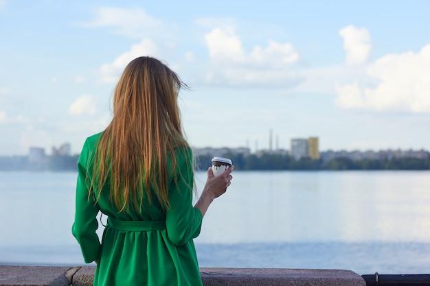 川でコーヒーを見ている女性