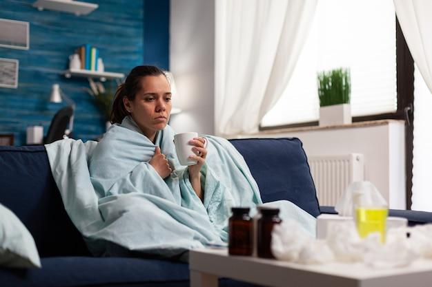 感染症や発熱のための風邪やインフルエンザの薬を飲む女性
