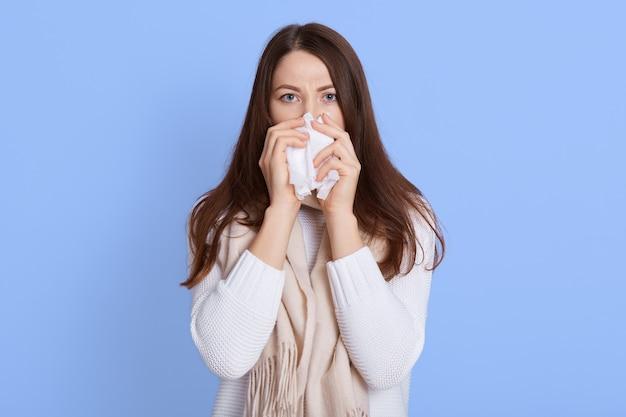 Женщина с простудой сморкается салфеткой из насморка