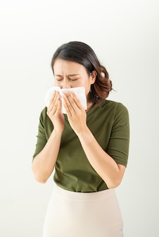 Woman with a cold blowing her runny nose with tissue