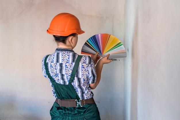 壁を塗るために色を選ぶ色見本を持つ女性