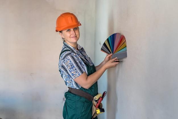 그림 벽에 대 한 색상을 선택하는 색상 견본을 가진 여자
