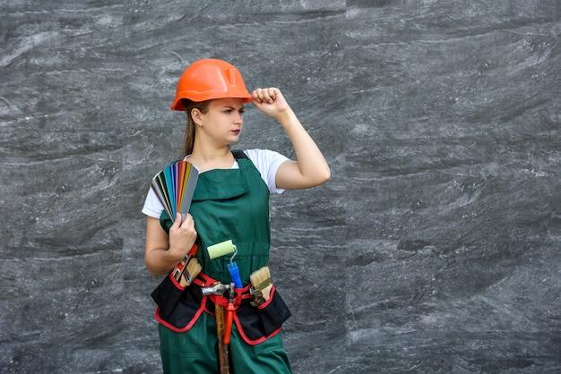 Женщина с образцом цвета. она в комбинезоне и шлеме позирует на абстрактном фоне