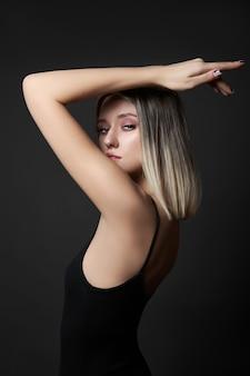 검은 배경에 금발 머리 색깔을 가진 여자.