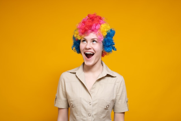 A woman with colored hair opened her mouth. on a yellow background. it's april fool's day.
