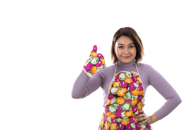 Woman with colorful apron gives thumb up