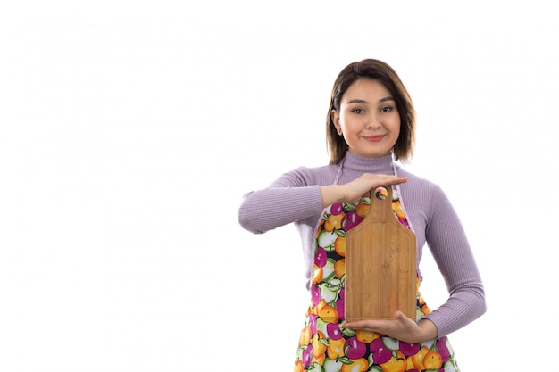 Woman with colorful apron holding cutting board