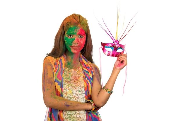 Женщина с красочным лицом держит карнавальную маску и празднует холи.