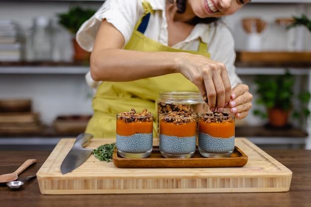 Donna con dolci sani e colorati budini di chia a base di latte di mandorle, estratto di spirulina blu, semi di chia, marmellata di mango pappaya e muesli fatto in casa. sul tavolo di legno in cucina a casa.