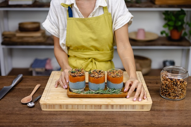 Woman with colorful healthy sweet deserts chia puddings made of almond milk, blue spirulina extract, chia seeds, pappaya mango jam and homemade granola. on wooden table in kitchen at home.