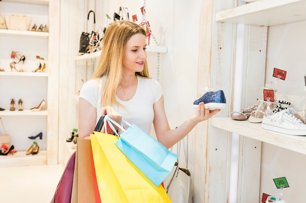 Woman with colorful shopping bags looking at shoe in shop