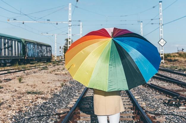 버려진 된 철도 트랙을 따라 걷는 화려한 우산을 가진 여자