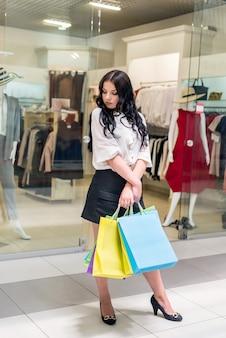 Женщина с красочными сумками позирует перед магазином одежды