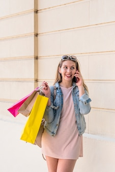 Woman with colourful shopping bags talking by phone at wall