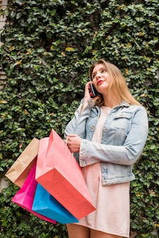 Woman with colourful shopping bags talking by phone outside