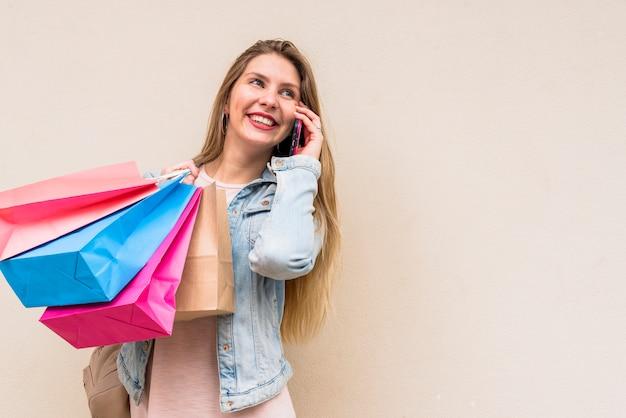 Donna con i sacchetti della spesa variopinti che parla dal telefono