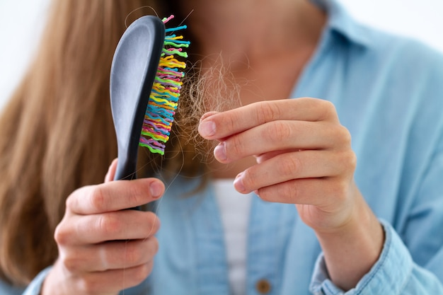 Woman with comb suffering from hair loss
